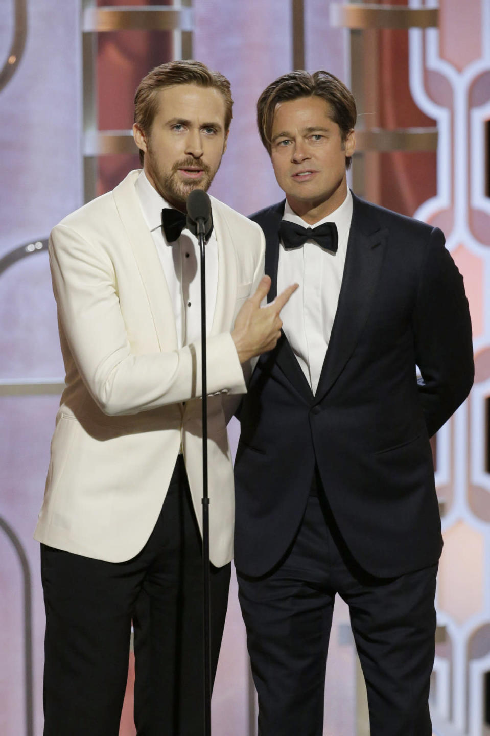 Ryan Gosling in a white tuxedo jacket with Brad Pitt, sporting some new side bangs, at the 73rd Golden Globe Awards.