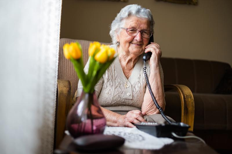 Old woman with gray white hair and glasses sitting in her armchair in her home and talking on wired phone as Australian government introduces smart phone coronavirus applications