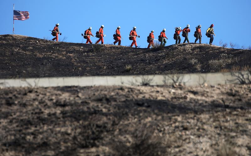 CANYON COUNTRY, CALIFORNIA - OCTOBER 25: Inmate firefighters march past an American flag, while led by a fire captain, as they work to put out hot spots from the Tick Fire on October 25, 2019 in Canyon Country, California. The fire has blackened 4,300 acres thus far with around 40,000 people under mandatory evacuation orders. The inmates are from one of the 44 state prison fire camps, where inmates perform firefighting duties during the wildland fire season, for credit for early release and minimal pay. (Photo by Mario Tama/Getty Images)