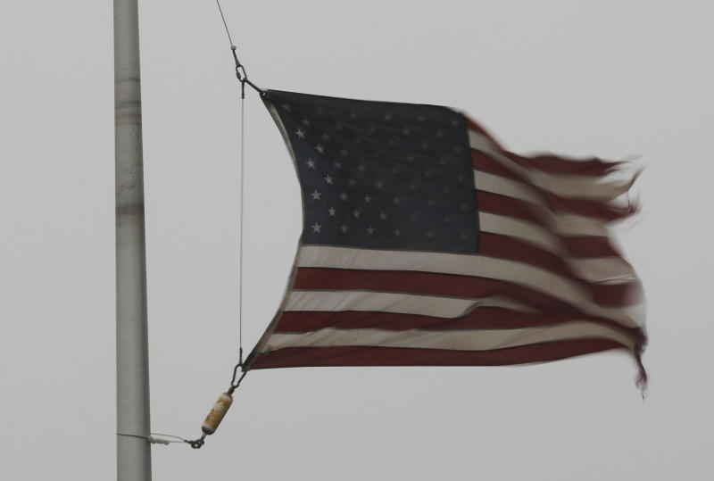 A flag is tattered in the wind of a severe thunderstorm at a farm credit office near Baldwin City, Kan., Sunday, April 27, 2014. Severe storms are expected in the area most of the day. (AP Photo/Orlin Wagner)