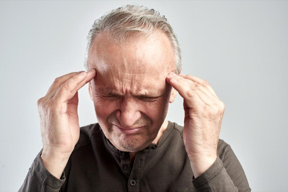 An old man touches his head. Headache. Alzheimer's disease