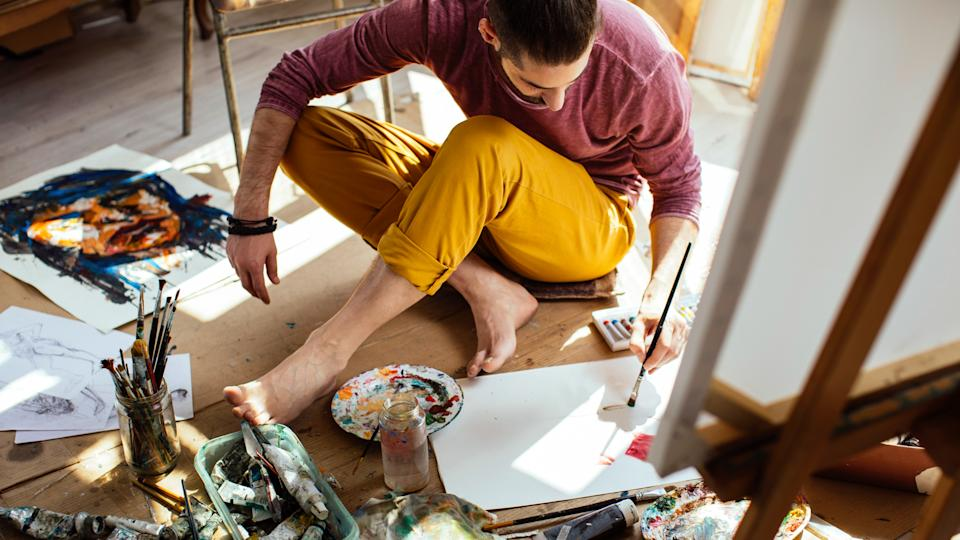 Art guy painting on a daylight in a bright studio sitting on the floor.