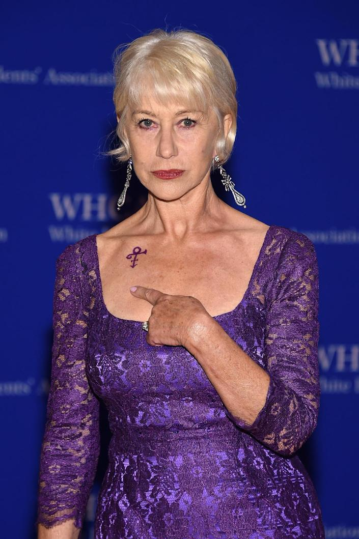 <p>Actress Helen Mirren indicates a symbol honoring the late musician Prince on her shoulder as she attends the the 102nd White House Correspondents' Dinner, April 30. <i>(Photo: Larry Busacca/Getty Images)</i></p>