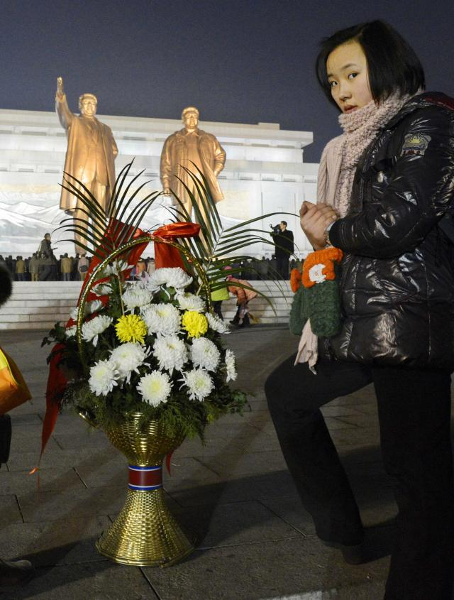A woman stands next to flowers near bronze statues of North Korea's late founder Kim Il Sung and late leader Kim Jong Il at Mansudae in Pyongyang