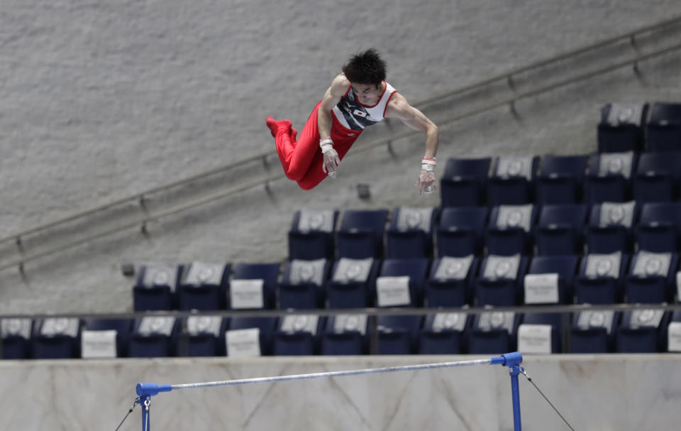 Kohei Uchimura of Japan competes in the bars of an international gymnastics meet in Tokyo on Sunday, Nov. 8, 2020. Gymnasts from four countries of China, Russia, U.S. and Japan performed in the meet at Yoyogi National Stadium First Gymnasium, a venue planned to be used in the Tokyo 2020 Olympics in the summer 2021. (AP Photo/Hiro Komae)