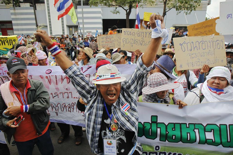 Farmers protest outside the temporary office of Thai Prime Minister Yingluck Shinawatra in Bangkok February 17, 2014. Hundreds of unpaid Thai rice farmers swarmed around the office on Monday, threatening to storm the building if the beleaguered premier did not come out and speak to them. The escalation of the protest by farmers, who have not been paid for crops sold to the government under a state rice-buying scheme that helped sweep Yingluck's Puea Thai Party to power, came as thousands of demonstrators seeking to unseat the prime minister surrounded the government's headquarters. REUTERS/Chaiwat Subprasom (THAILAND - Tags: POLITICS CIVIL UNREST AGRICULTURE BUSINESS)