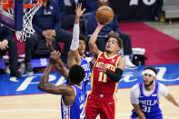 Atlanta Hawks' Trae Young (11) goes up for a shot against Philadelphia 76ers' Joel Embiid (21), Matisse Thybulle (22) and Seth Curry (31) during the second half of Game 5 in a second-round NBA basketball playoff series, Wednesday, June 16, 2021, in Philadelphia. (AP Photo/Matt Slocum)