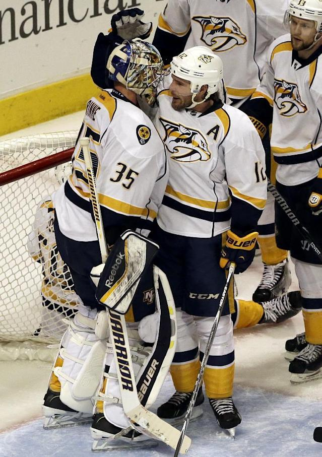 Nashville Predators goalie Pekka Rinne (35) celebrates with Mike Fisher (12) after they defeated the Chicago Blackhawks 3-2 during an NHL hockey game in Chicago, Friday, March 14, 2014. (AP Photo/Nam Y. Huh)