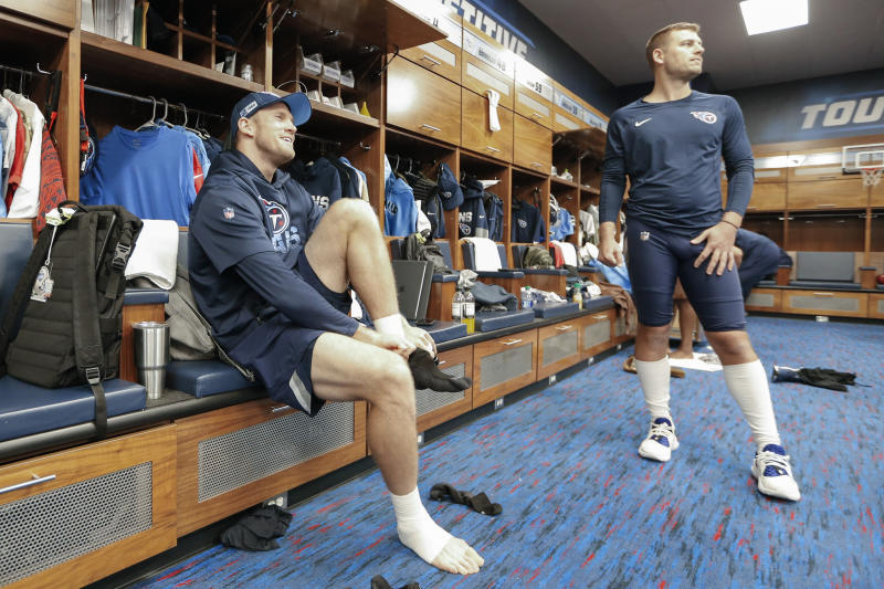 Tennessee Titans quarterback Ryan Tannehill, left, and punter Brett Kern, right, talk in the locker room before practice. (AP Photo/Mark Humphrey)