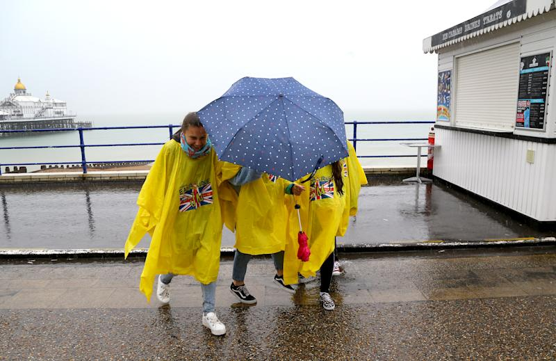 German exchange students brave torrential rain on the promenade in Eastbourne, Sussex (Picture: PA)