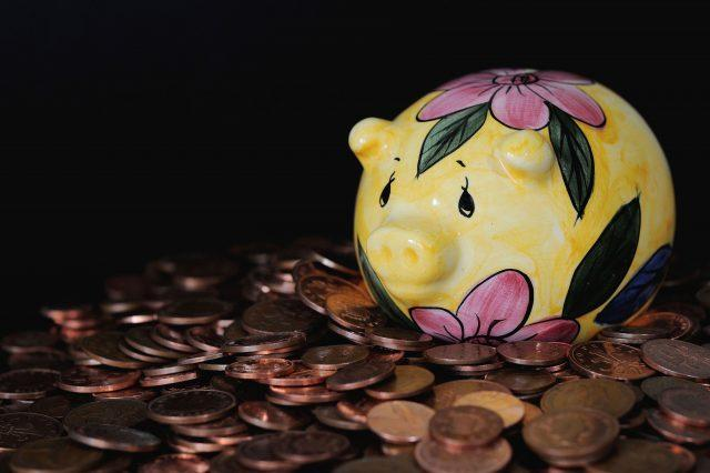 A piggy bank on a pile of coins