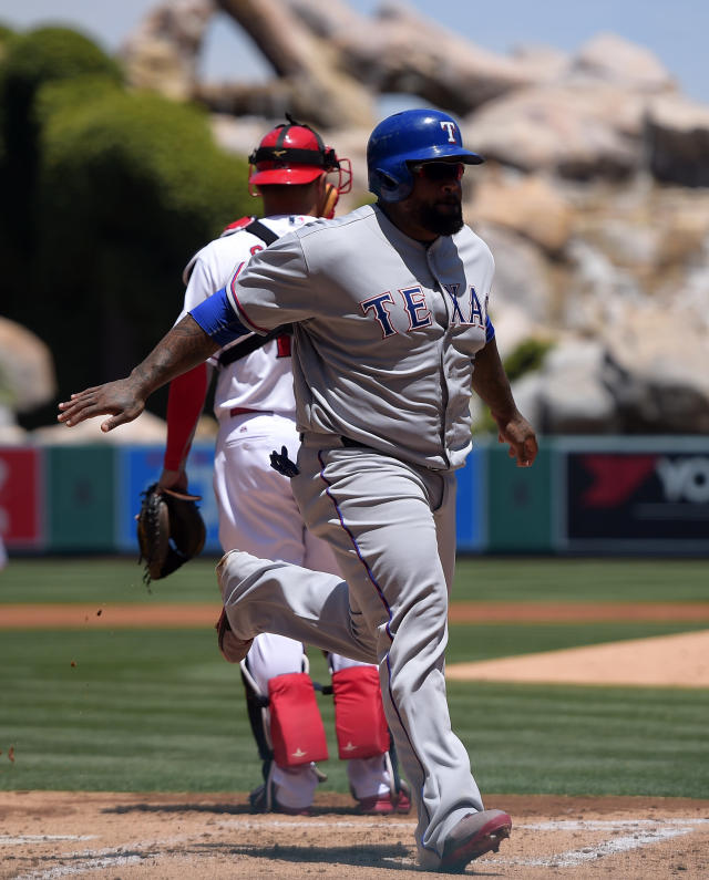 Texas Rangers' Prince Fielder, right, scores on a sacrifice fly hit by teammate J.P. Arencibia as Los Angeles Angels catcher Hank Conger looks on during the first inning of a baseball game on Sunday, May 4, 2014, in Anaheim, Calif. (AP Photo/Mark J. Terrill)