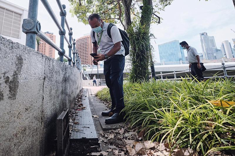 NEA dengue inspection officers checking drains for mosquito breeding. (PHOTO: National Environment Agency)