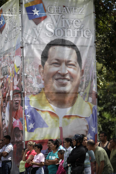 Supporters of Venezuela's President Hugo Chavez stand by a banner of him during a small gathering of supporters near the military hospital in Caracas, Venezuela, Tuesday, Feb. 26, 2013. The government said last week that the country's ailing president was continuing unspecified medical treatments at the military hospital in Caracas. Chavez's sudden return to Venezuela after more than two months of cancer treatments in Cuba has fanned speculation that the president could be preparing to relinquish power and make way for a successor and a new election. (AP Photo/Ariana Cubillos)