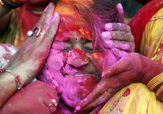 Students of Rabindra Bharati University apply colored powder to a fellow student's face as they celebrate Holi, also known as the festival of colors in Kolkata, March 6, 2012.