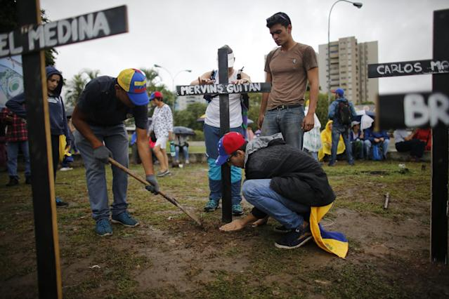 <p>People place crosses, representing people who have died during the most recent opposition protest movement, on the side of a highway during a national sit-in against President Nicolas Maduro, in Caracas, Venezuela, Monday, May 15, 2017. (AP Photo/Ariana Cubillos) </p>