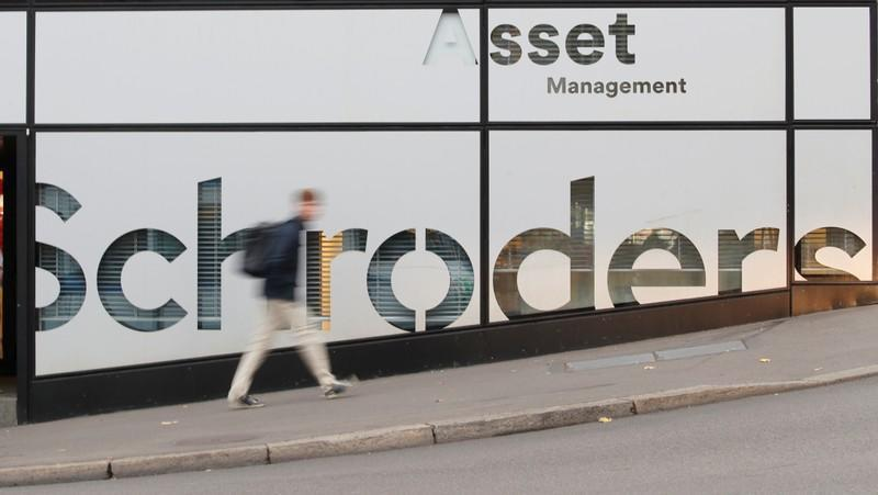 A man walks past the logo of investment management company Schroders in Zurich