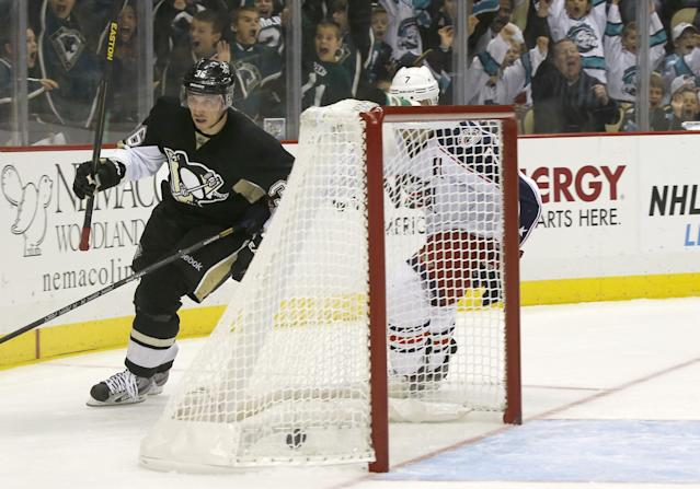 Pittsburgh Penguins' Jussi Jokinen, of Finland, left, skates behind the net as Columbus Blue Jackets' Jack Johnson pursues after scoring his third goal in the second period of the NHL hockey preseason game on Saturday, Sept. 21, 2013, in Pittsburgh. (AP Photo/Keith Srakocic)