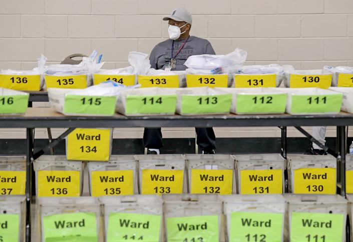 Tim McMurty, a temporary voting machine technician for the  City of Milwaukee, sits behind containers of ballots yet to be counted at the presidential election recount at the Wisconsin Center in Milwaukee on Sunday.