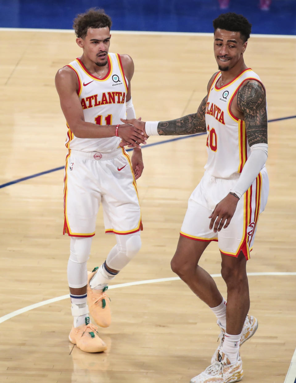 Atlanta Hawks guard Trae Young (11) and forward John Collins (20) congratulate each other after defeating the New York Knicks 103-89 in Game 5 of an NBA basketball first-round playoff series Wednesday, June 2, 2021, in New York. (Wendell Cruz/Pool Photo via AP)