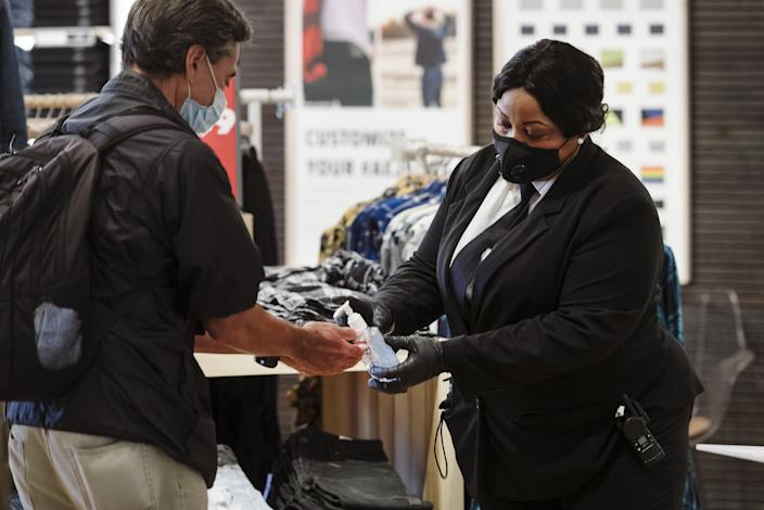 A security guard wearing a protective mask gives a shopper hand sanitizer at the entrance to an American Eagle Outfitters Inc. store at Westfield San Francisco Centre in San Francisco, California, U.S., on Thursday, June 18, 2020. (Michael Short/Bloomberg via Getty Images)