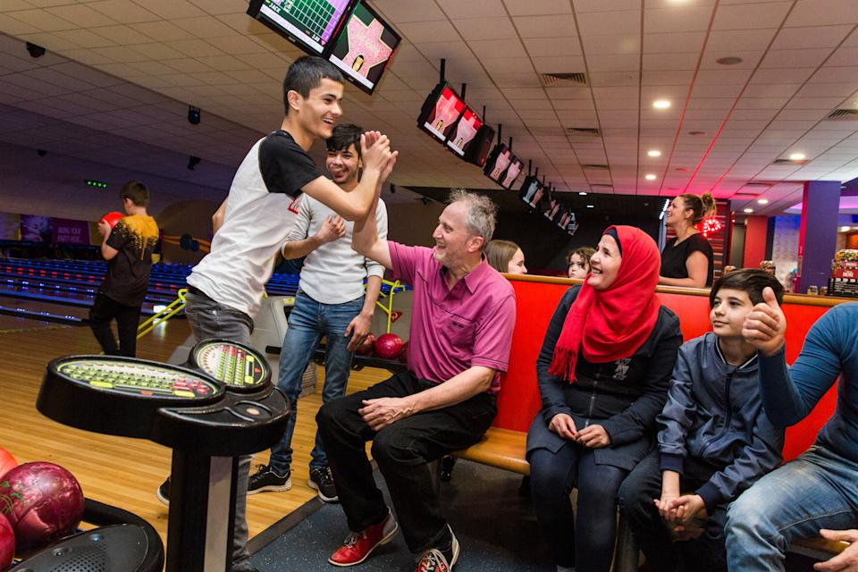 <p>Sixteen-year-old Haitham Daour gives Ged Cavanagh a high five after a strike at a bowling alley in Bury</p>Andrew McConnel