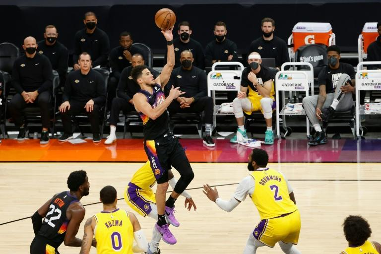 Phoenix star Devin Booker shoots over the Los Angeles Lakers' Andre Drummond in game five of their playoff series