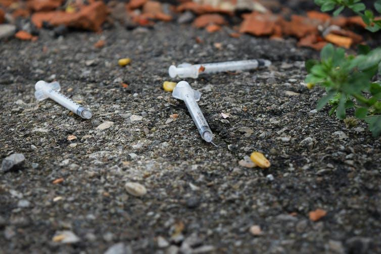 Used drug syringes on the pavement outdoors.