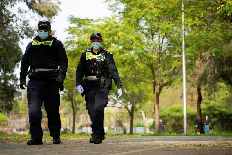 Police officers patrol the grounds outside a public housing tower, reopened following a COVID-19 lockdown, in Melbourne
