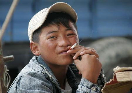 A 16-year-old Tibetan boy smokes in Dangxiong country