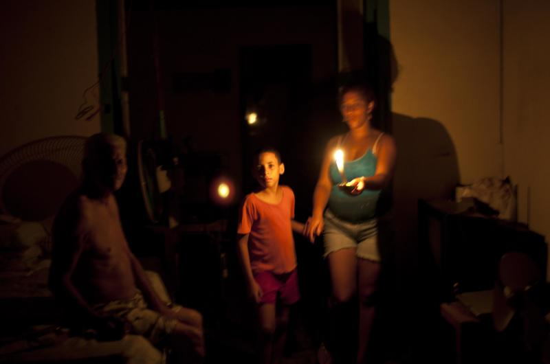 People walk at home uising candles for light during the blackout in Havana, Cuba, Sunday, Sept 9, 2012. Power failed across a large swath of western Cuba on Sunday night, including the capital, Havana, and the popular tourist resort of Varadero, plunging millions of people into darkness. (AP Photo/Ramon Espinosa)