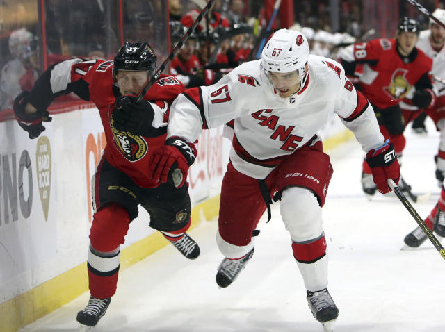 Ottawa Senators Jonathan Davidsson(17) and Carolina Hurricanes Trevor van Riemsdyk (57) race for the puck during second period NHL hockey action in Ottawa, Saturday Nov. 9, 2019. (Fred Chartrand/The Canadian Press via AP)