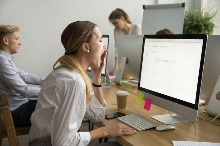 A woman yawns at her desk at work.