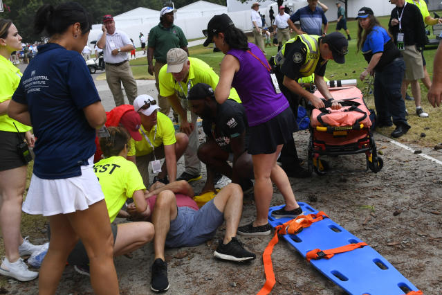 A spectator is tended to after a lightning strike left several injured during the third round of the Tour Championship golf tournament Saturday, Aug. 24, 2019, in Atlanta. (AP Photo/John Amis)