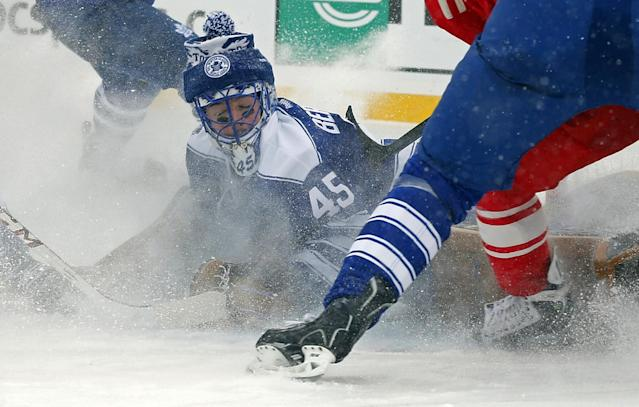 Toronto Maple Leafs goalie Jonathan Bernier (45) stops a shot on goal during the second period of the Winter Classic outdoor NHL hockey game against the Detroit Red Wings at Michigan Stadium in Ann Arbor, Mich., Wednesday, Jan. 1, 2014. (AP Photo/Paul Sancya)