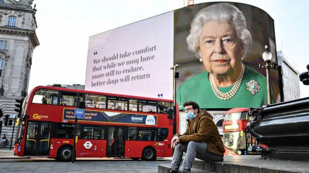 PHOTO: A man wearing a face mask sits in front of an image of Queen Elizabeth II with quotes from her broadcast to the nation on the coronavirus epidemic displayed on screens in Piccadilly Circus, on April 09, 2020, in London, England. (Peter Summers/Getty Images)