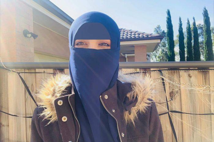 A woman wearing jacket outside standing in front of a fence