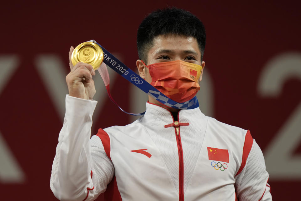 Li Fabin of China celebrates on the podium after winning the gold medal and setting an Olympic record in the men's 61kg weightlifting event, at the 2020 Summer Olympics, Sunday, July 25, 2021, in Tokyo, Japan. (AP Photo/Luca Bruno)