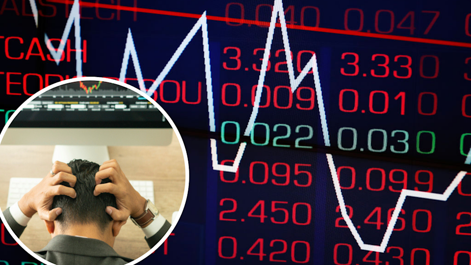 Trader with head in his hands, stock market ticker wall all in red.