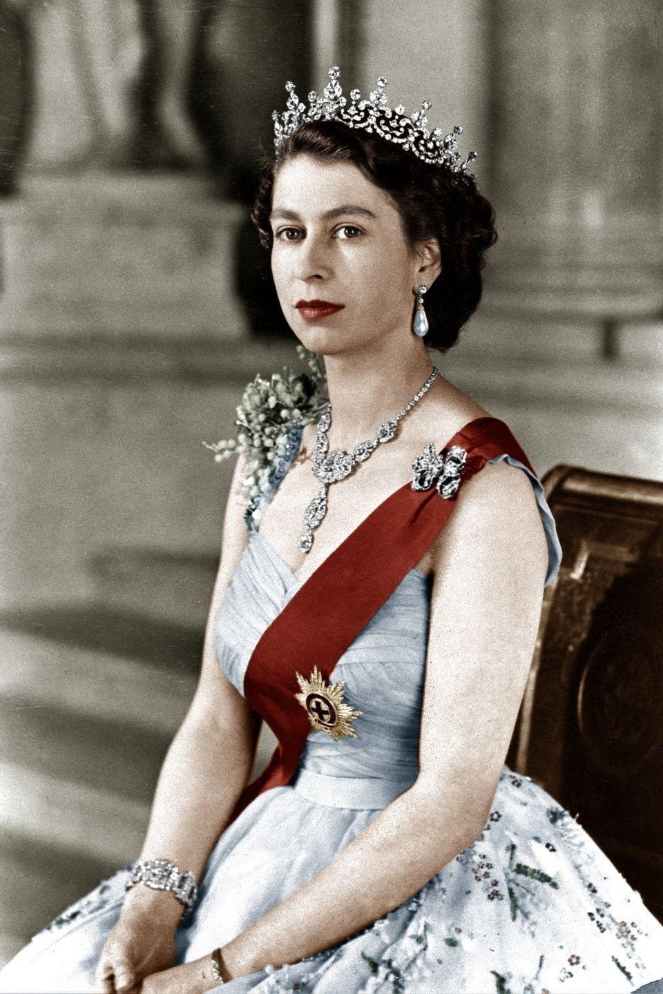 <p>In a sleeveless and embellished blue dress, diamond earrings, necklace, and a bracelet–topped off with a sparkly diamond tiara. </p>