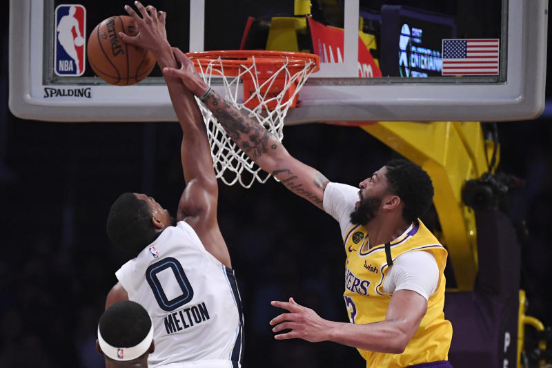 Los Angeles Lakers forward Anthony Davis, right, hits Memphis Grizzlies guard De'Anthony Melton after blocking his shot during the second half of an NBA basketball game Friday, Feb. 21, 2020, in Los Angeles. The Lakers won 117-105. (AP Photo/Mark J. Terrill)