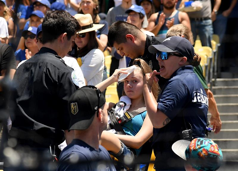 A young woman receives treatment after being hit by a foul ball off the bat of Cody Bellinger at Dodger Stadium on June 23