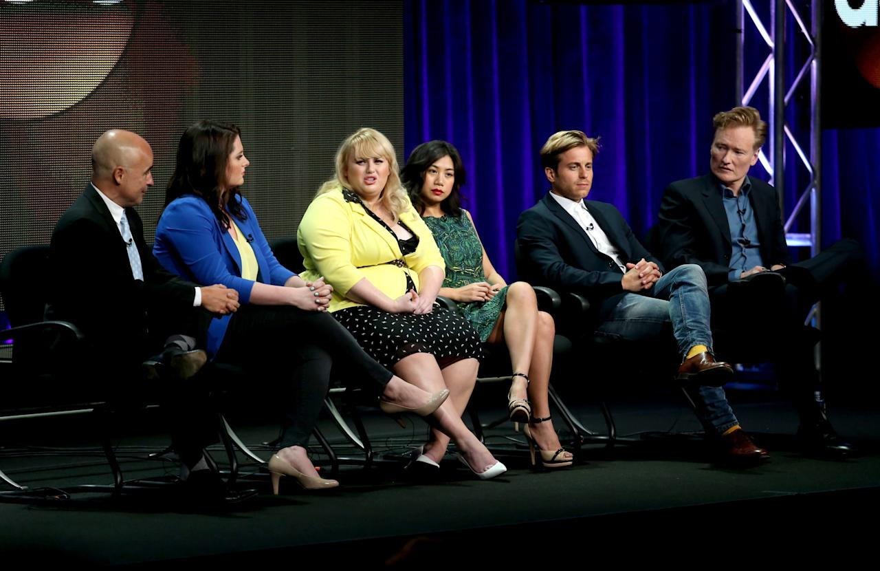 "BEVERLY HILLS, CA - AUGUST 04: (L-R) Executive producer John Riggi, actress Lauren Ash, writer/actress Rebel Wilson, actors Liza Lapira, Kevin Bishop and executive producer Conan O'Brien speak onstage during the ""Super Fun Night"" panel discussion at the Disney/ABC Television Group portion of the Television Critics Association Summer Press Tour at the Beverly Hilton Hotel on August 4, 2013 in Beverly Hills, California. (Photo by Frederick M. Brown/Getty Images)"