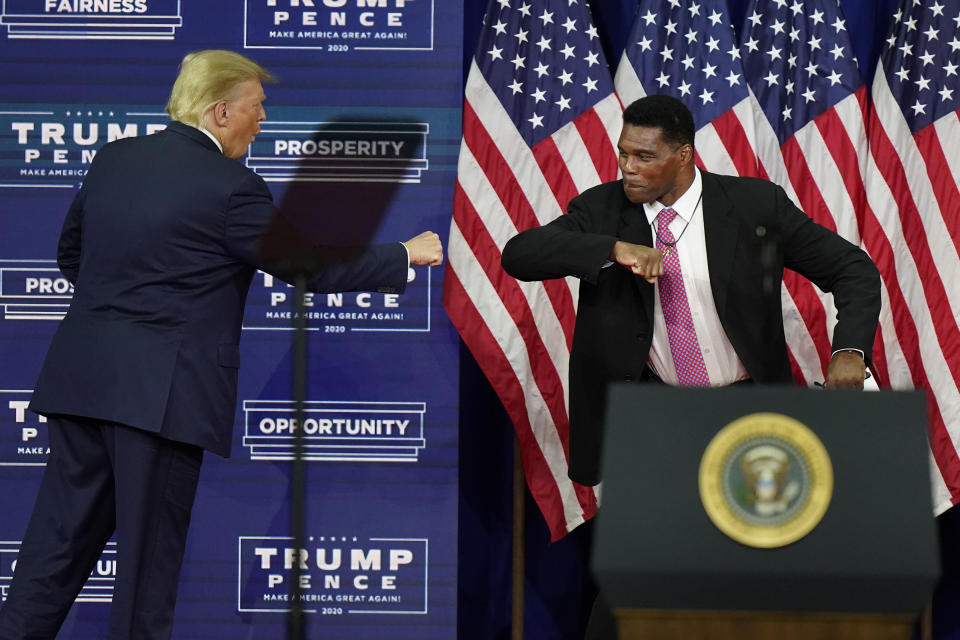 FILE - In this Sept. 25, 2020, file photo, President Donald Trump elbow bumps with Herschel Walker during a campaign rally in Atlanta. Walker appears to have a coveted political profile for a potential Senate candidate in Georgia. (AP Photo/John Bazemore, File)