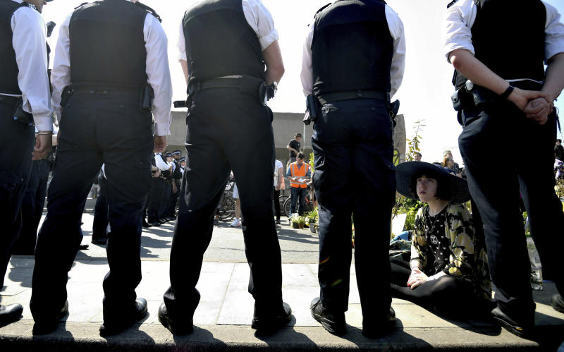 Police speak to a demonstrator on the main thoroughfare on Waterloo Bridge in central London, Saturday April 20, 2019. Climate protesters with the environmental pressure group Extinction Rebellion are once again shutting down parts of London using civic disobedience to urge residents and government to do more to protect the Earth from rising temperatures.(Victoria Jones/PA via AP)
