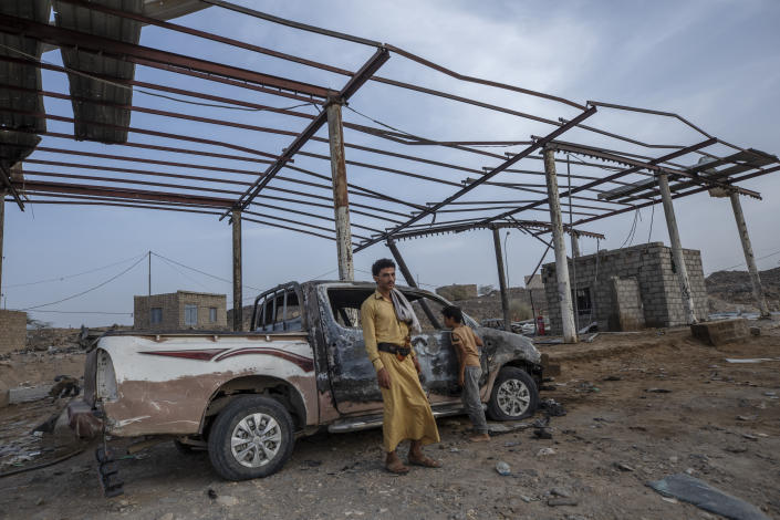 A man and boy look at damages in the aftermath of a ballistic missile and an explosive-laden drone fired by Yemen's Houthi rebels that hit a fuel station on June 5, 2021, killing two-year-old Liyan Taher and her father 32-year-old Taher Farag in the Rawdha neighborhood of the central city of Marib, Yemen, Sunday, June 20, 2021. (AP Photo/Nariman El-Mofty)