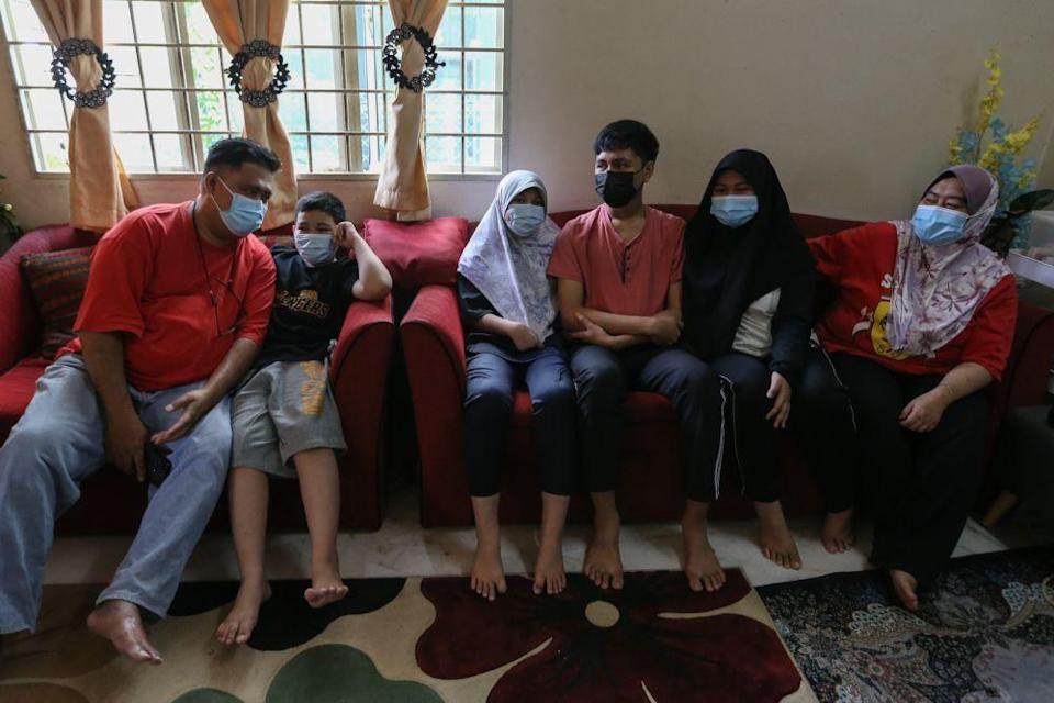 The four siblings, who lost their parents to Covid-19, are being taken care of by their uncle and aunt Normawati Ahmad (extreme right). — Picture by Ahmad Zamzahuri
