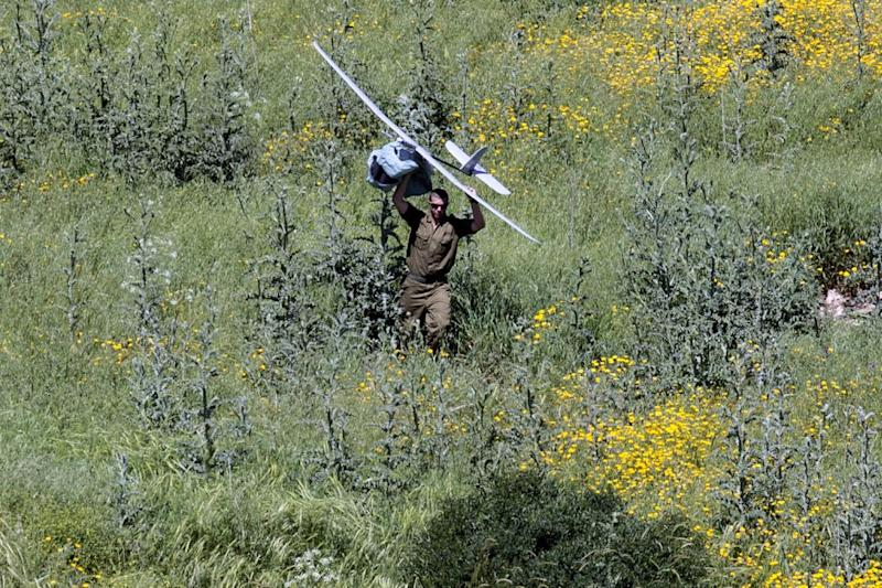 An Israeli soldier carries an unmanned drone used for monitoring purposes along the border between Israel and Lebanon on April 21, 2014