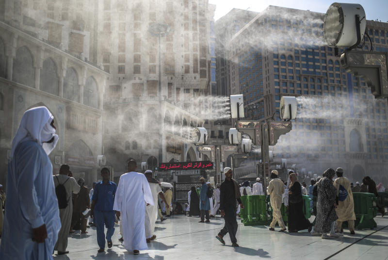 FILE - In this Sept. 15, 2015 file photo, water is sprayed over Muslim pilgrims to cool them down during the afternoon heat as they walk outside the Grand Mosque in the holy city of Mecca, Saudi Arabia. A new study released Monday, May 4, 2020, says 2 to 3.5 billion people in 50 years will be living in a climate that historically has proven just too hot to handle. Currently about 20 million people live in places with an annual average temperature greater than 84 degrees (29 degrees Celsius) — far beyond the temperature sweet spot. That area is less than 1% of the Earth's land, and it is mostly near the Sahara Desert and includes Mecca, Saudi Arabia. (AP Photo/Mosa'ab Elshamy, File)