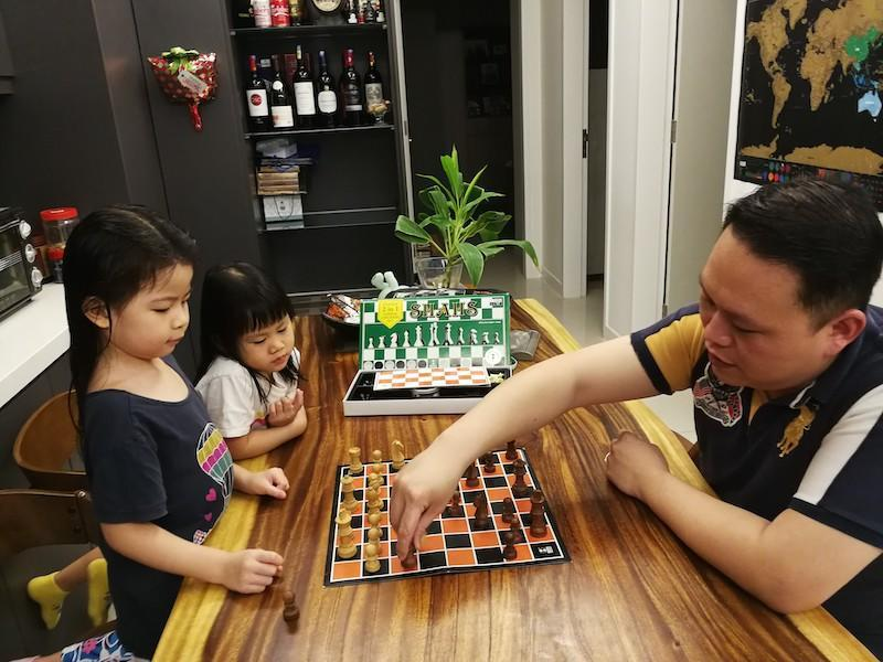 Ng (right) guiding his daughters on the basic strategies of chess. — Picture courtesy of Ng Hong Haw